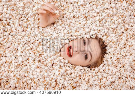 Girl Portrait In Popcorn. The Face In Popcorn. Woman In Popcorn And Eats It With Appetite.