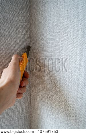 Hand Holding, Cutting Gray Wallpaper Side With Yellow Construction Knife In Corner Of Room, Remodeli