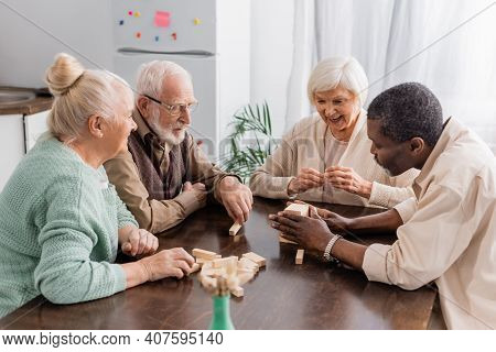 Excited Senior Woman Smiling While Playing Tower Wood Blocks Game With Interracial Friends.