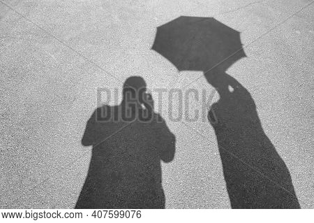 Shadows On The Pavement. Male Shadow And The Shadow Of A Woman With An Opened Umbrella. Close-up.
