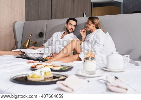 Young Interracial Couple In Bathrobes Sitting Near Tasty Food On Blurred Foreground On Hotel Bed.