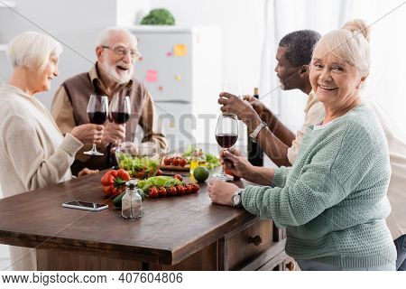 Happy Senior Woman Holding Glass Of Red Wine And Smiling Near Multicultural Retired Friends On Blurr
