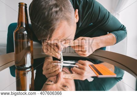 Young Addicted Junkie Man Sniffing Or Snorting Cocaine Lines On Mirror Through Rolled Banknote. Narc