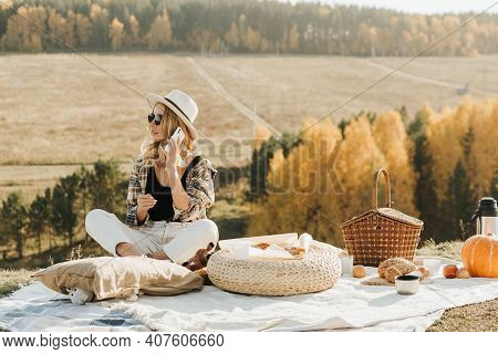 Blonde Woman Resting In Nature Alone. A Picnic Alone. Call To Loved Ones. Communication At A Distanc
