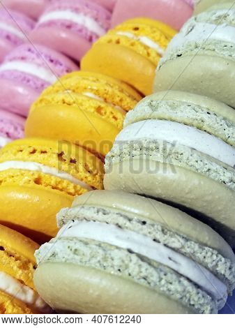 Rows Of Pink, Orange And Pale Green Macron Cookies.