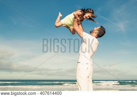 Cheerful Excited Dad Holding Girl And Throwing Hands Up In Air. Handsome Father And Little Daughter