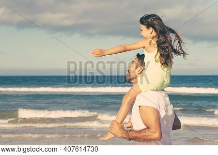 Excites Little Daughter Sitting On Fathers Neck And Making Flying Hands. Excited Dad And His Girl Wa
