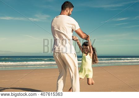 Dad Having Fun With Daughter On Beach, Playing Active Games, Holding Girls Hands And Spinning Around