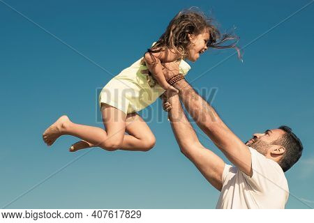 Joyful Dad Holding Excited Girl And Throwing Hands Up In Air. Handsome Father And Little Daughter Ha