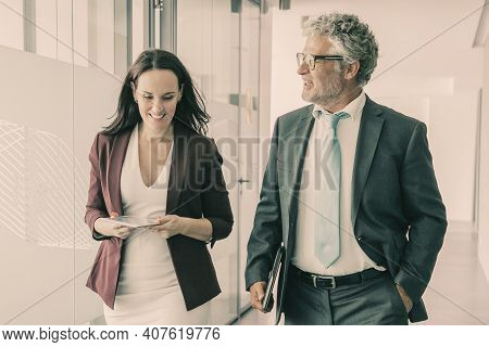 Experienced Businesspeople Walking Through Office Corridor And Talking. Professional Grey-haired Ceo