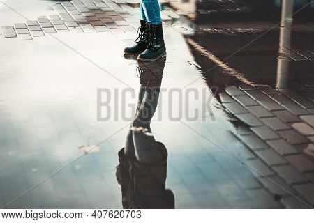 A Woman In Boots Stands Near The Puddles. Reflections Of The Sky In Puddles. Lower Angle. The Concep