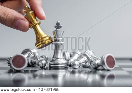 Businessman Hand Moving Gold Chess King Figure And Checkmate Opponent During Chessboard Competition.