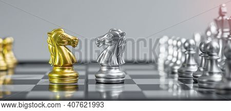 Gold And Silver Chess Knight (horse) Figure On Chessboard Against Opponent Or Enemy. Strategy, Confl