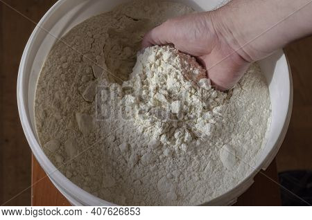 Man Dips His Hand Into Large Plastic Bucket Of Wheat Flour. Hand Dipped In Flour. View From Above At