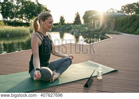 Change Your Life. Beautiful Middle Aged Woman Sitting In Lotus Pose And Smiling While Doing Yoga On