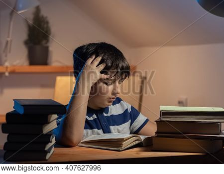 The Idea Of A Childs Participation In Learning. The Focused Face Of A Boy Reading A Book In His Room