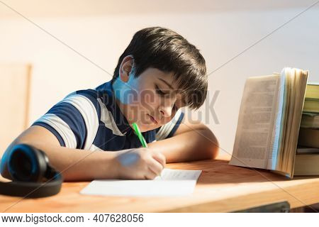 Calligraphy Classes. Boy In Front Of A Book While Busy Rewriting Text. Horizontal Composition