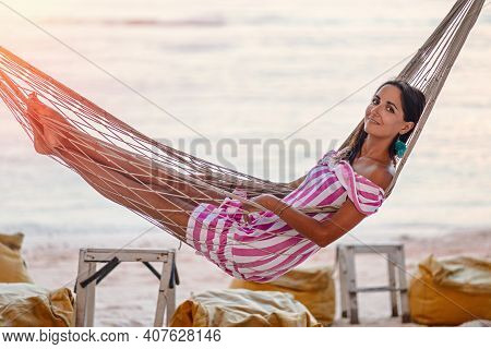 Resort. A Young Happy Beautiful Woman In A Striped Dress Is Lying On A Wicker Hammock. Side View. In