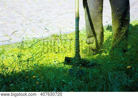 Cutting Lush Green Grass In The Park. Beautiful Nature Background. Lawn Care Work In Progress Concep