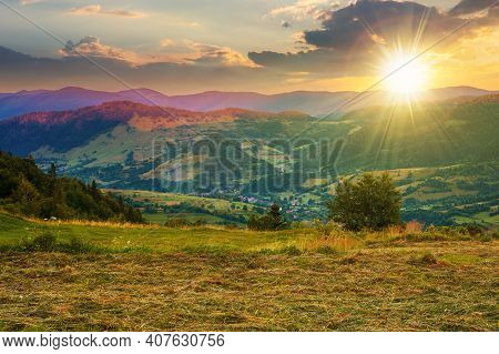 Mountainous Rural Landscape At Sunset. Grassy Meadow On Top Of A Hill. Clouds Above The Ridge In Eve