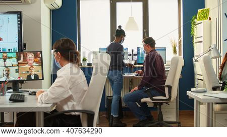 Business Woman Discussing On Webcam Using Wireless Headphone With Remotely Partners Wearing Protecti