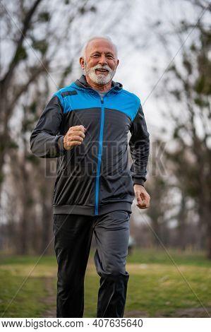 Happy Senior Man Is Jogging In Park.