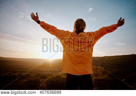 Rear View Of Young Man Standing On Mountain With Outstretched Arms Feeling Relaxed After Morning Run