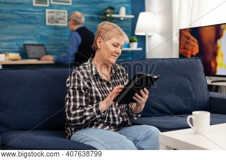 Smiling Senior Woman With Tablet Pc Resting On Sofa Elderly Woman Using Moder Technoloy Tablet Pc In