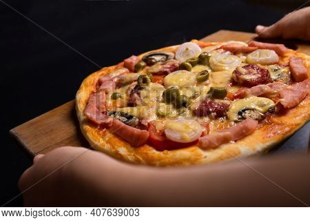 Hads Serving Pizza With Chees And Sausage On Wooden Tray, On Black Background.