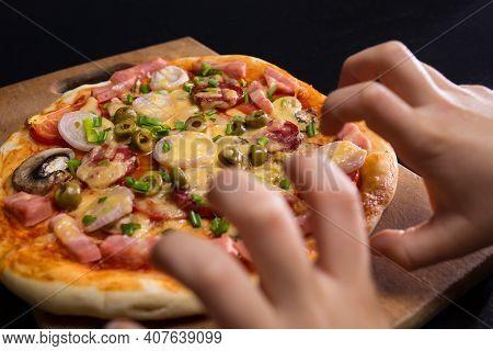 Children Hands Greedy Taken Pizza From Wooden Board, On A Black Background.