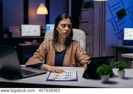 Entrepreneur Using Tablet Pc While Working From Dark Office Working On Deadline. Business Woman Work