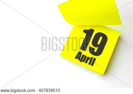 April 19th. Day 19 Of Month, Calendar Date. Close-up Blank Yellow Paper Reminder Sticky Note On Whit