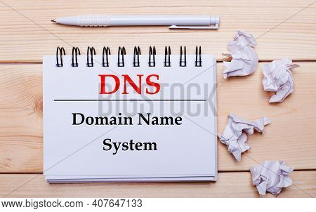 On A Wooden Background, A White Notebook With The Inscription Dns Domain Name System, A White Pen An