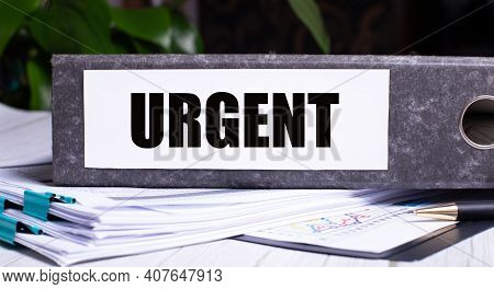 The Word Urgent Is Written On A Gray File Folder Next To Documents. Business Concept