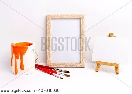 Mockup Of Blank Photo Frame And Canvas On Easel. Paint Bucket And Brushes. Concept Of Creativity, Ar
