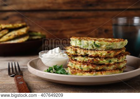Delicious Zucchini Fritters With Sour Cream Served On Wooden Table, Closeup