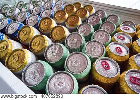 Beer Cans Fresh From The Fridge. Lots Of Aluminum Cans In The Ice In The Open Fridge. Drops Of Water