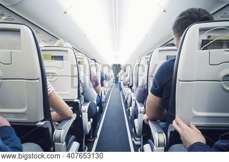 Interior Of Airplane With Passengers On Seats. Flying In Economy Class Aircraft Low-cost Airline. In