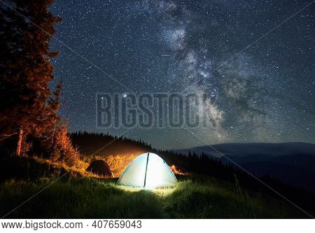 Two Tourists Tents, One Of Which Shining White Light On Mountain Grass Hill With View On Milky Way G