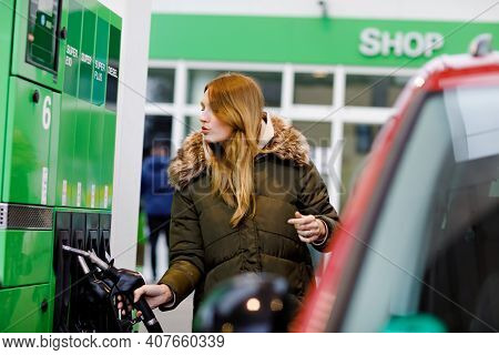 Young Caucasian Woman At Self-service Gas Station, Hold Fuel Nozzle And Refuel The Car With Petrol,