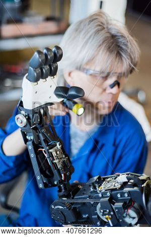 The Man Assembles A Human-like Robot And Mends His Hand