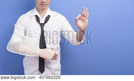 Young Businessman With An Injured Arm In A Sling Over Blue Background In Studio, Insurance And Healt