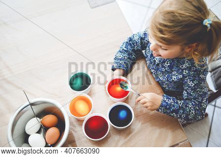 Closeup Of Little Toddler Girl Coloring Eggs For Easter. Close-up Of Child Looking Surprised At Colo