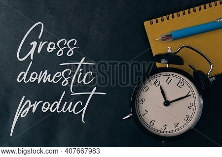 Top View Of Pen, Notebook And Clock Over Black Background Written With Gross Domestic Product