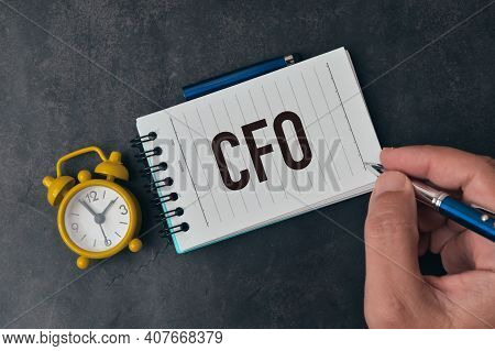 Top View Of Man Hand Holding Pen And Writing Cfo Stands For Chief Financial Officer