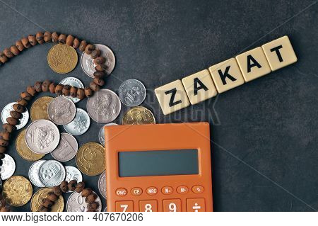 Top View Of Coins, Calculator And Prayer Beads And Scrabble Letters With Text Zakat