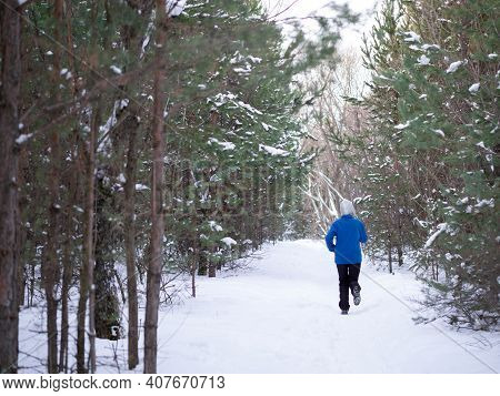 Winter Outdoor Pursuits. Woman In Blue Warm Sportwear Jogging On The Snow In The Parkland, Back View