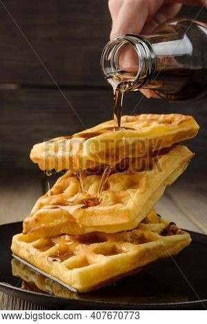 Vienna Waffles With Maple Syrup Close-up. The Syrup Is Poured From The Bottle Onto The Waffle.