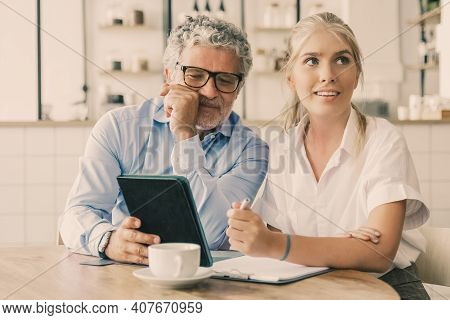 Mature Mentor Explaining Work Details To Young Intern. Business Man Showing Tablet Screen To Young F