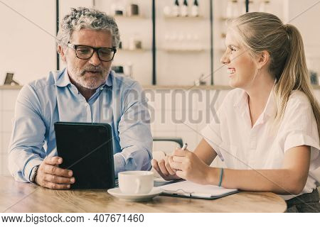 Friendly Mature Mentor Explaining Project Detail To Joyful Intern. Business Man Using Tablet And Tal